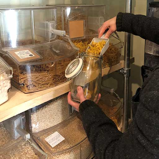 Filling empty container with pasta to reduce plastic shopping